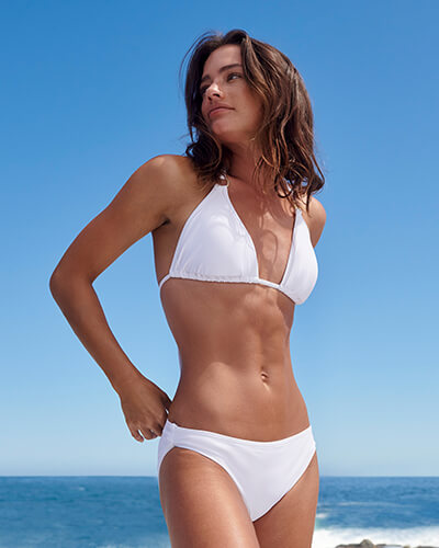 White bikini top with metal ring detail on straps, paired with white bikini bottoms