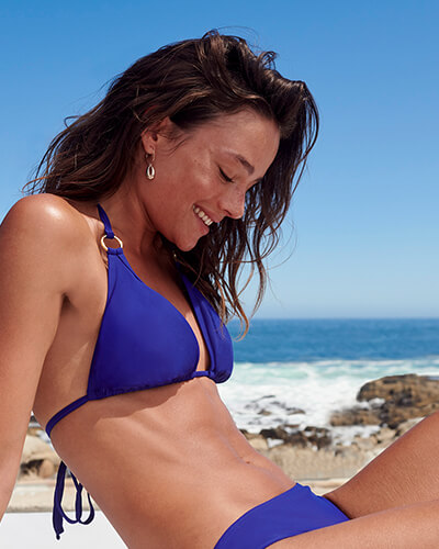 Blue bikini top with metal ring detail on straps, paired with blue bikini bottoms