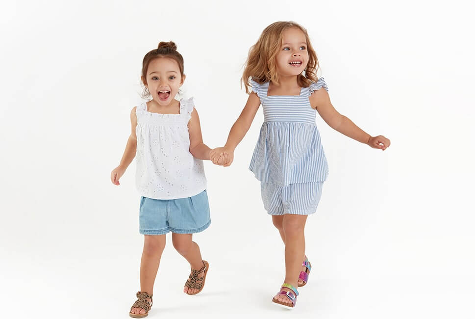 White broderie anglaise top with ruffle edge shoulder straps, worn with loose light blue denim shorts. Sleeveless blue and white stripe top with frilled edge shoulder straps. Comes with matching stripe shorts