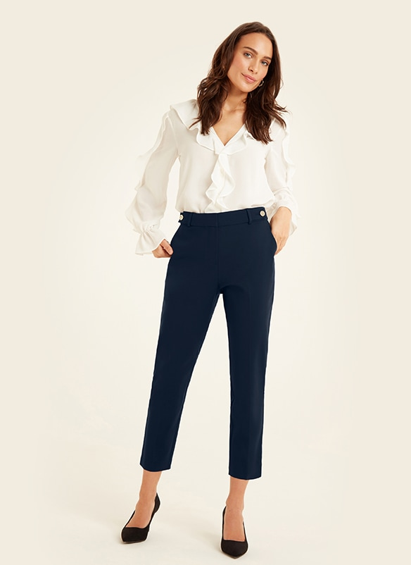 White blouse with ruffle detail collar, front and sleeves. Trousers are slim-fit, calf-length, with 2 metal buttons on waistband