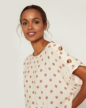 Cream top with pink spots and large buttons on the shoulders