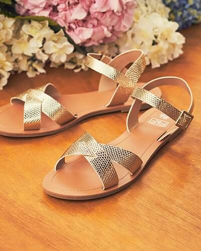 Flat, gold, cross-front strap sandals with side buckle