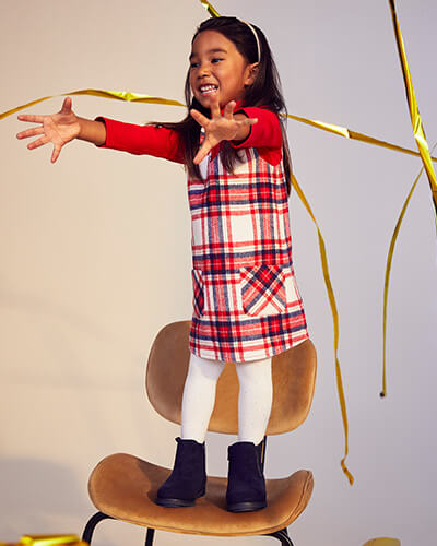 Red and white check pinafore with some navy lines, worn with long sleeve red top and white tights