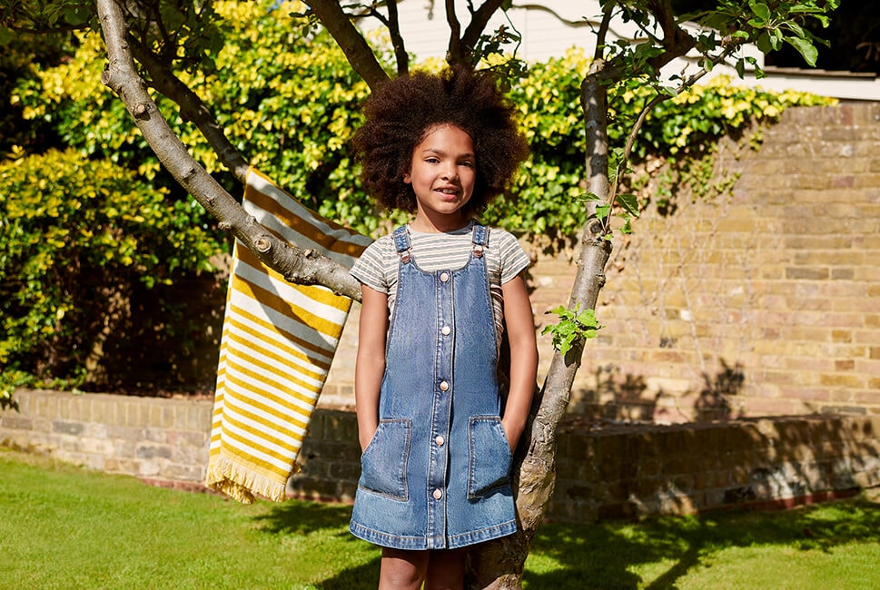 Button-through denim pinafore paired with a grey, white and brown striped T-shirt