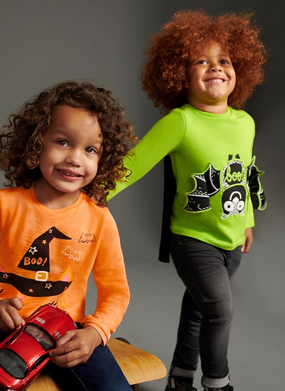 Long sleeve, neon lime top with black cape, and black and white upside down bat motif with 3D wings. Halloween top is long sleeve, neon orange, with black witch's hat and bats design