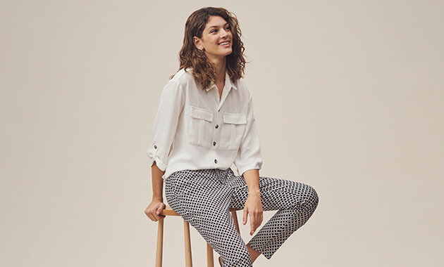 Loose white shirt with dark buttons, 2 chest pockets and 3 quarter length, buttoned roll-up sleeves. Trousers have a black and white geometric criss-cross print