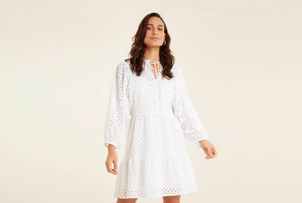 Long sleeve, loose-fitting, layered, short white dress with Schiffli lace pattern tiered top layer, and thin fabric tie at the neck