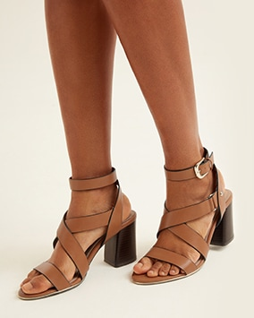 High block heel tan sandals with strap over toes, straps crossing over foot and buckled strap at ankle