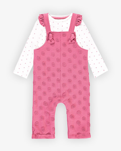 Rose pink dungarees with textured towelling spots and ruffle edging on shoulder straps. Comes with long sleeve pink spotted white top