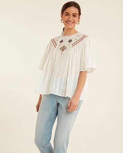 Round neck, loose white top with elbow-length loose sleeves. Fabric has thin stripe detailing and Aztec-style salmon pink and black embroidery