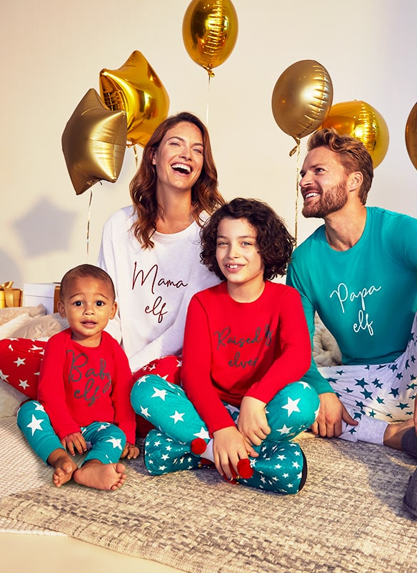 All pjs are long sleeved with elf-related wording. Adult pjs 1 have a white top and red bottoms with white stars. Adult pjs 2 have a turquoise top and white marl bottoms with turquoise stars. Kids' pjs have a red top and turquoise bottoms with white stars