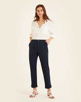 White, loose-fitting shirt with 2 chest pockets. Dark navy trousers are in a smart, chino-style fabric with side pockets and belt loops