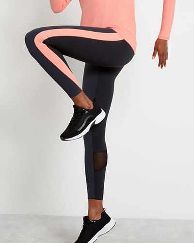 Navy leggings have a peachy-pink stripe along the side