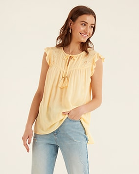 Lemon longline top with frilled cap sleeves, floral embroidery on shoulders and tassel-ended tie at neck