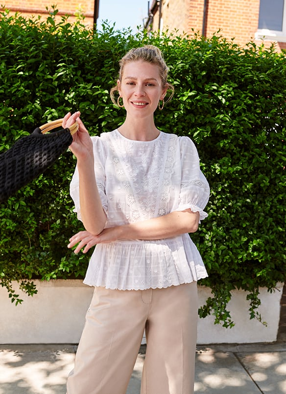 White puffy sleeved top with Broderie anglaise detail and frill trim at the bottom and the end of the sleeves