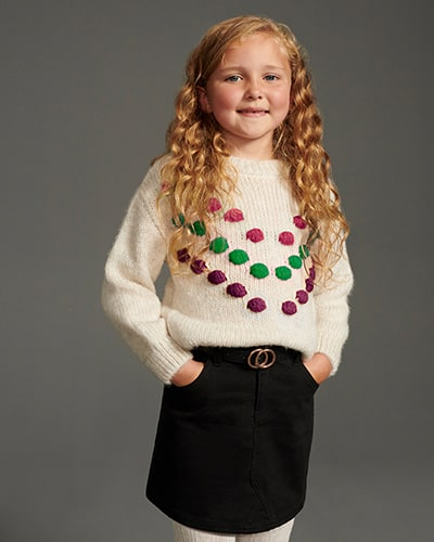 Cream rib knit with pink, green and purple pom-poms on the front