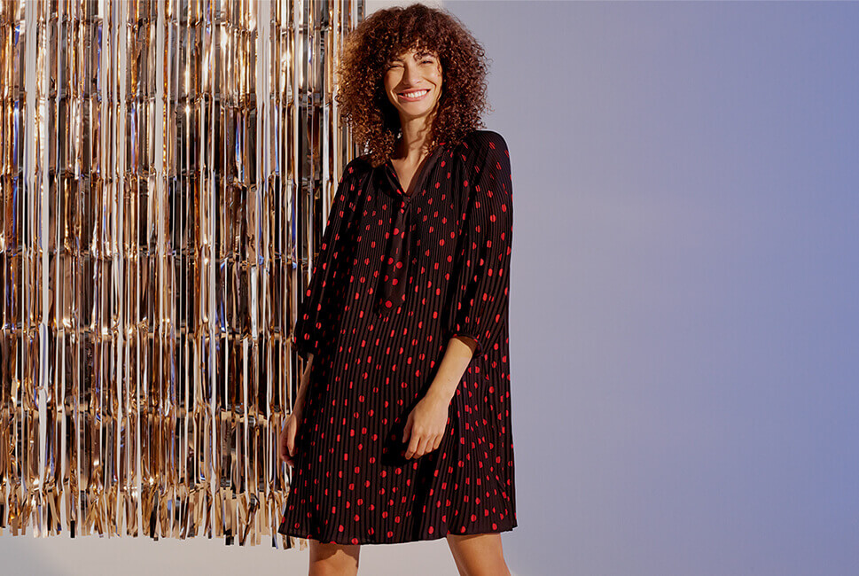 Black, loose fit pleated tunic with red polka dots, elbow-length sleeves and necktie detail
