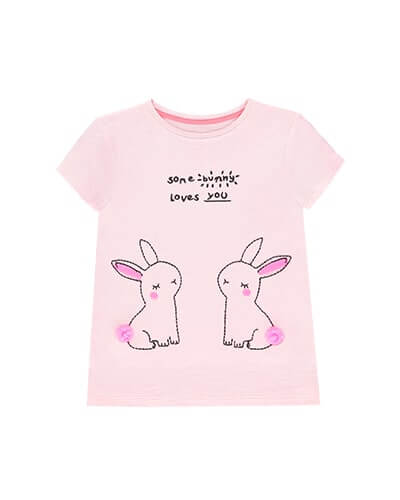 Pale pink T-shirt has words some bunny loves you, with 2 cute bunny outlines, with pink pom-pom tails