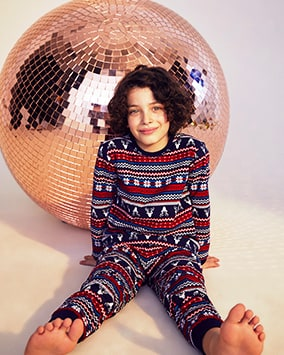 Long sleeve knitted pyjamas with repeating horizontal red, white, blue and navy multi patterns, including reindeer motif, flowers and zig zags