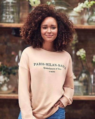 Ladies' peach sweater with black wording on chest saying 'Paris, Milan, Barca, Quadrilatero d'Oro, La Moda'