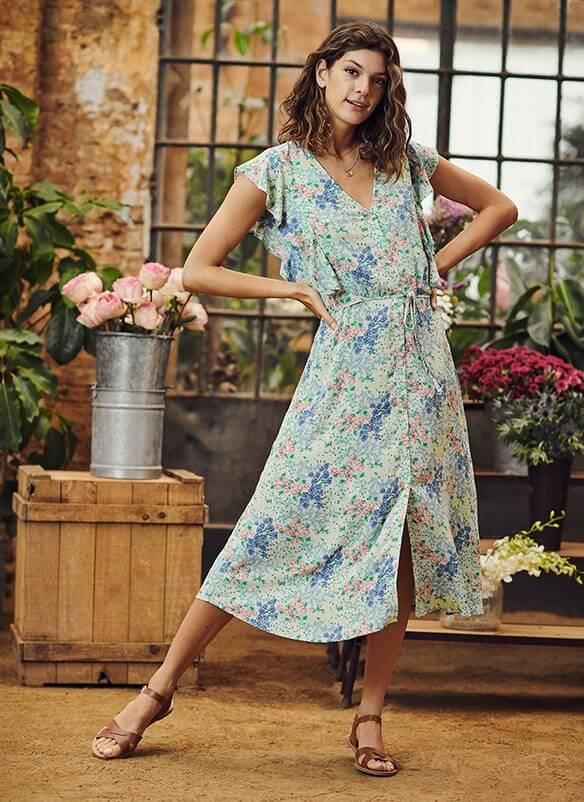 Long, button-through, V-neck dress with loose cap sleeves and thin fabric tie belt. Print is of blue, pink and green flowers on a white background