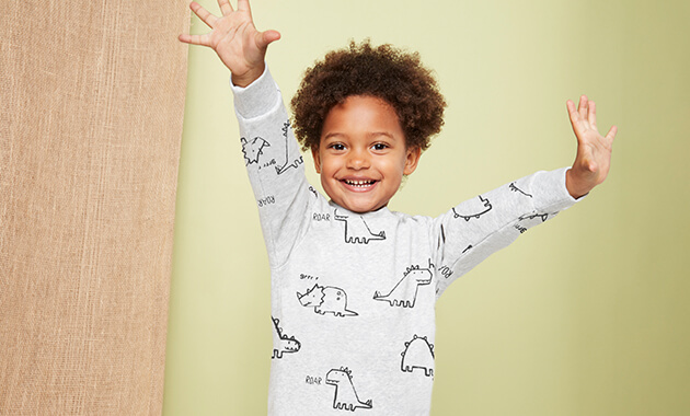 Pale grey sweater with black line drawings of cute dinosaurs and the words hi, roar and grrr