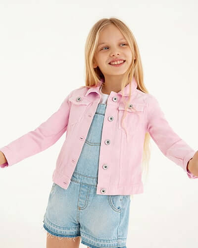 Pale pink denim jacket with silvery buttons and chest pockets. Cut-off style shorts playsuit is in light blue denim