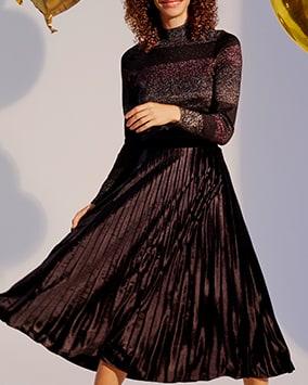Turtleneck lurex jumper with sparkly dark grey, black and purple block stripes, worn with black, velvet pleated midi skirt