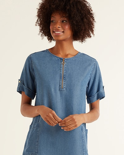 Light blue denim shift dress with round neck, zip down the middle of the chest, folded short sleeves and 2 pockets on the front