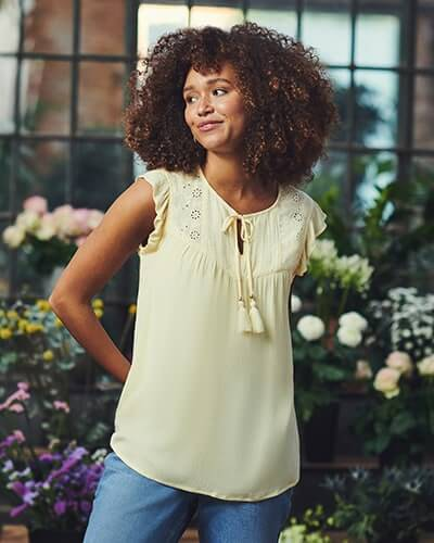 Yellow floaty vest with schiffli detail on chest, frilly sleeves and tassle tie neck