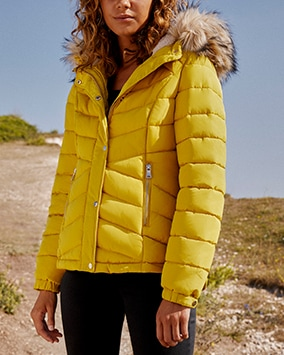 Short chartreuse yellow padded jacket with furry-lined hood and 2 zip pockets