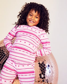 Long sleeve knitted pyjamas with repeating horizontal light pink, fuchsia pink and white multi patterns, including reindeer motif, flowers and zig zags