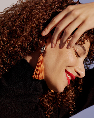 Oval textured metal earrings with long orange tassel
