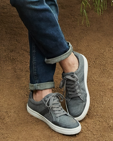 Light grey, lace-up trainers with darker grey stripe detail, and white sole