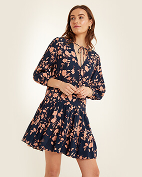 Long sleeve, v-neck, short navy dress with peach floral print, gathered tiers and thin fabric tie at the neck