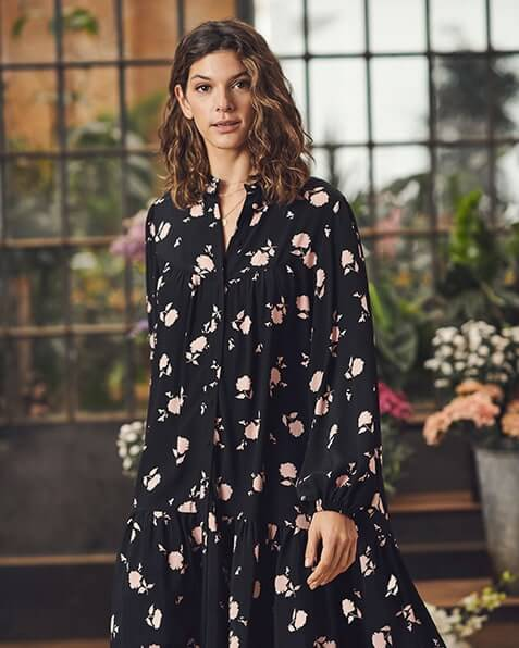 Knee length, long sleeve, round neck, loose-fit, button-through dress with gathering detail at chest above hem. Print is of peach flowers on a black background