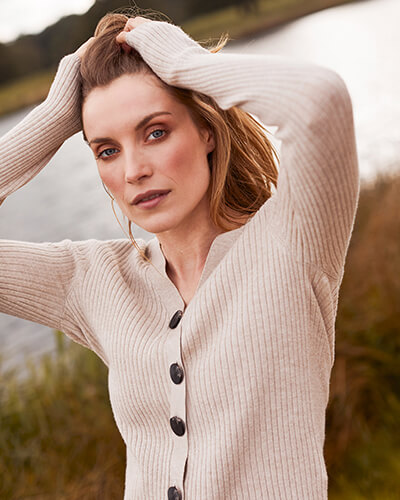 Cream cardigan with vertical stitch detail and large brown buttons