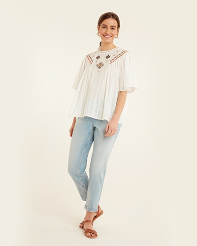 Round neck, loose white top with elbow-length loose sleeves. Fabric has thin stripe detailing and Aztec-style salmon pink and black embroidery. Jeans are light wash blue