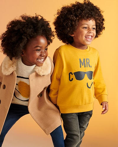 Double breasted camel brown coat with furry collar. Sweater shown is mustard yellow with black graphics saying 'Mr Cool', with black sunglasses representing the double o