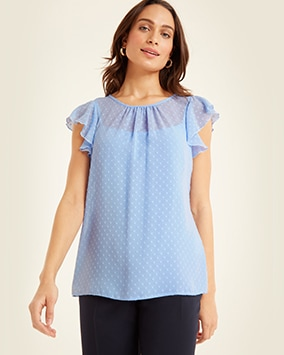 Round neck, sheer, cornflower blue spotted top with ruffle cap sleeves, layered over a vest top