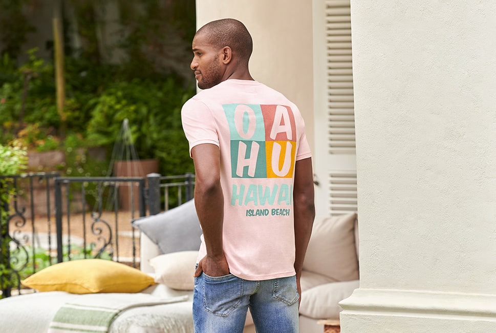 Light pink T-shirt with 'OAHU' in a multicoloured grid on the back and 'Hawaii Island Beach' in brightly coloured text under