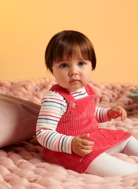 Red cord pinafore, worn with long sleeve white top with multicoloured stripes and white tights