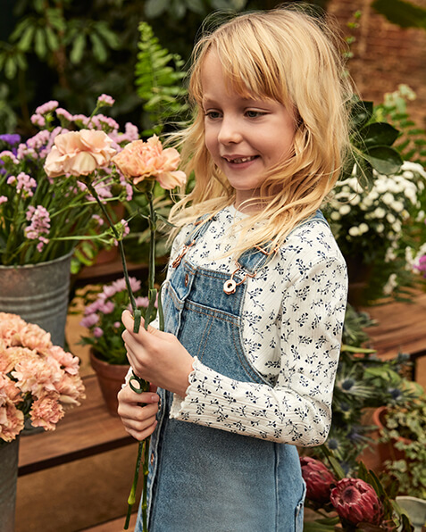 Button-through, blue denim pinafore dress. Comes with long sleeve, white ribbed top with blue floral print