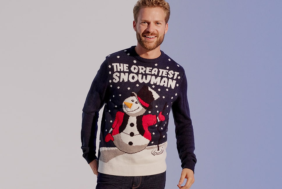 Navy jumper with a snowy scene featuring a snowman dressed as a circus ringmaster, with the wording 'The greatest snowman'