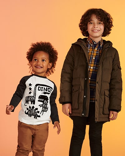 White top with long black sleeves and black dinosaur graphics. Brown, parka-style padded coat