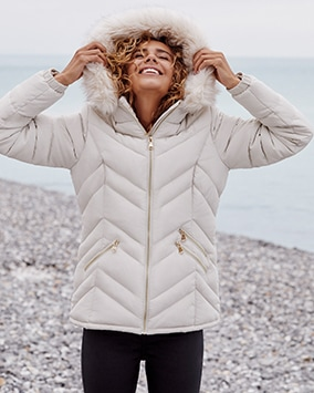 White padded zip up coat with furry-lined hood and 3 zip pockets