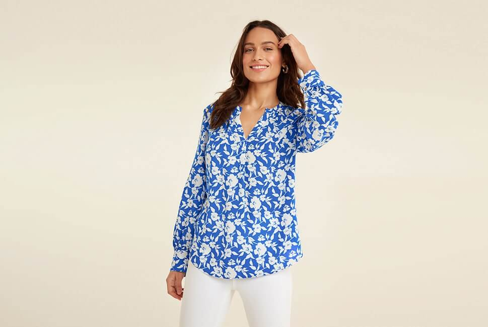 Long sleeve, V-neck sky blue top with white floral print and gathered, buttoned cuffs