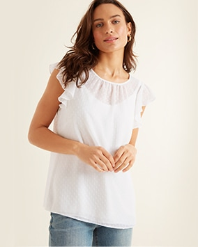 Round neck, sheer, white spotted top with ruffle cap sleeves, layered over a vest top