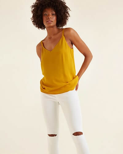 Orange, loose-fitting silky vest top. White jeans are tight-fitting, calf-length with rips at knees and raw hems