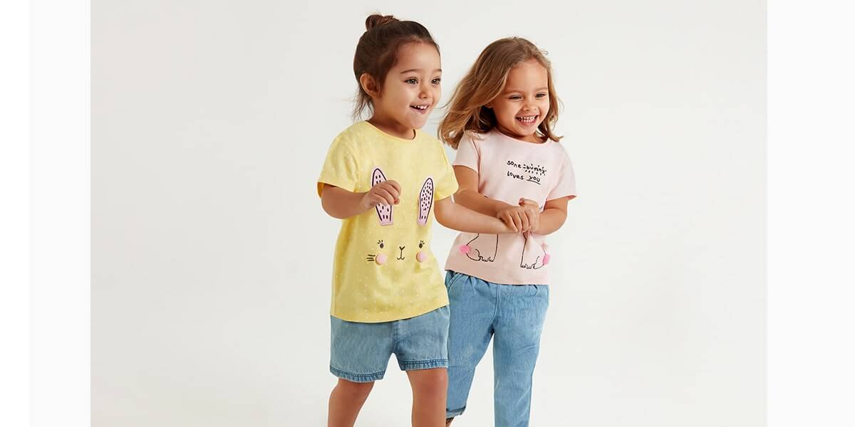 Yellow T-shirt has white spots and pink bunny ears and face on front, with pink pom-pom cheeks. Pale pink T-shirt has words some bunny loves you, with 2 cute bunny outlines, with pink pom-pom tails
